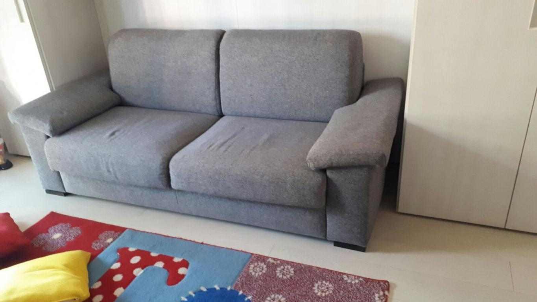 Divano-letto in tessuto di colore grigio